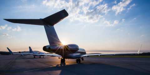 A private business jet parked on an airport ramp at sunset